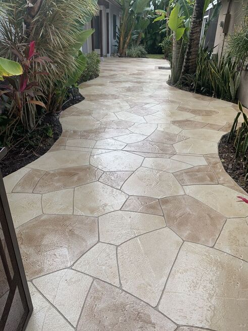 Beautiful concrete overlay walkway curving through garden