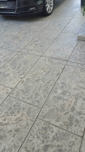 Picture of stamped concrete driveway in a modern large tile design stained in gray color tones overlay design.