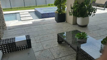 Picture of a patio overlooking swimming pool.  Deck is finished in a modern stamped concrete design.