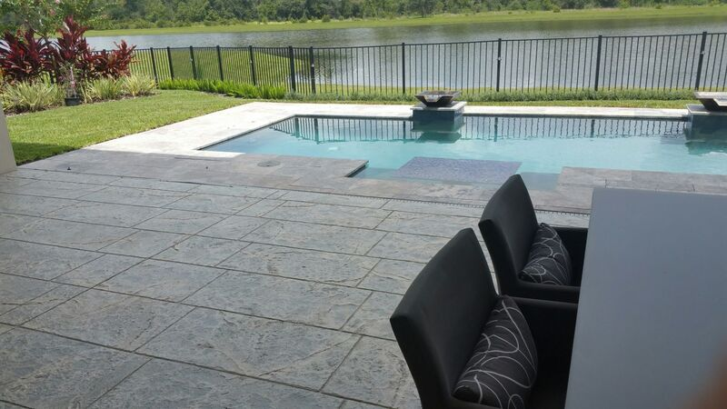 stamped concrete patio in modern home overlooking pool and conservation area